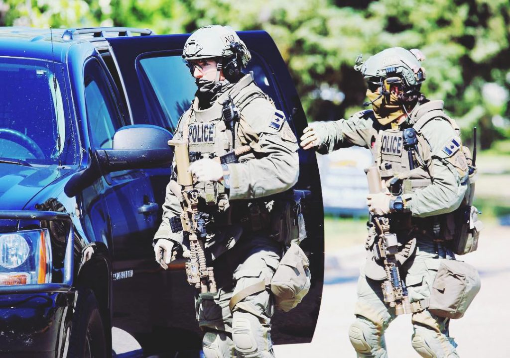 RCMP (Royal Canadian Mounted Police) officers wearing PICO Plate Carriers from Tyr Tactical. They're going after a barricaded suspect who earlier had shot a police officer.